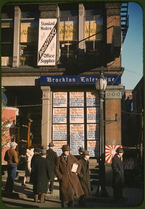 Headlines posted in street-corner window of newspaper office (Brockton Enterprise). Brockton, Massachusetts, December 1940. Reproduction from color slide. Photo by Jack Delano. Prints and Photographs Division, Library of Congress