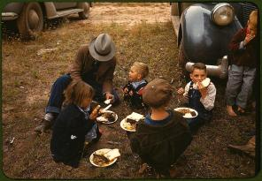 Homesteader and his children eating barbeque at the New Mexico Fair. Pie Town, New Mexico, October 1940. Reproduction from color slide. Photo by Russell Lee. Prints and Photographs Division, Library of Congress