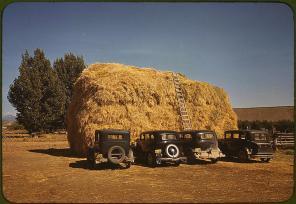 Hay stack and automobile of peach pickers. Delta County, Colorado, 1940. Reproduction from color slide. Photo by Russell Lee. Prints and Photographs Division, Library of Congress