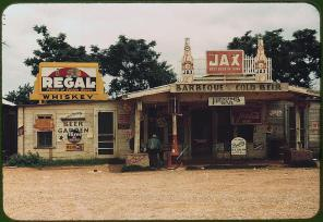 """A crossroads store, bar, """"juke joint,"""" and gas station in the cotton plantation area. Melrose, Louisiana, June 1940. Reproduction from color slide. Photo by Marion Post Wolcott. Prints and Photographs Division, Library of Congress"""