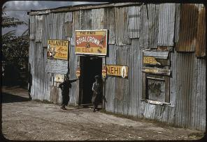 """African American migratory workers by a """"juke joint"""". Belle Glade, Florida, February 1941. Reproduction from color slide. Photo by Marion Post Wolcott. Prints and Photographs Division, Library of Congress"""