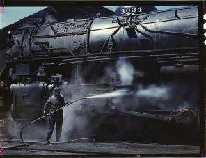 """Mrs. Viola Sievers, one of the wipers at the roundhouse giving a giant """"H"""" class locomotive a bath of live steam. Clinton, Iowa, April 1943. Reproduction from color slide. Photo by Jack Delano. Prints and Photographs Division, Library of Congress"""